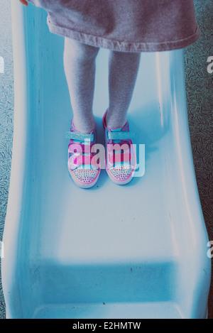 Ragazza permanente sulla diapositiva, indossando variopinti sneakers, sezione bassa Foto Stock