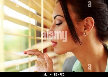 Bella imprenditrice cercando nella finestra di office Foto Stock