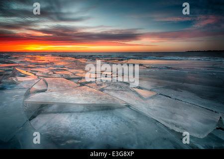 Lastre di ghiaccio pila lungo le rive del lago di St. Clair nel sud-est Michigan, che riflettono i colori del crepuscolo. Foto Stock