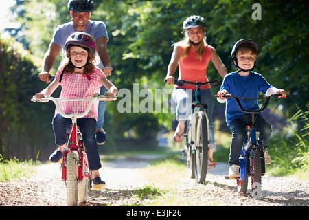 La famiglia sul tragitto in bicicletta in campagna Foto Stock