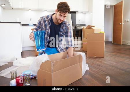 Uomo che si muove nella nuova casa e scatole di disimballaggio Foto Stock