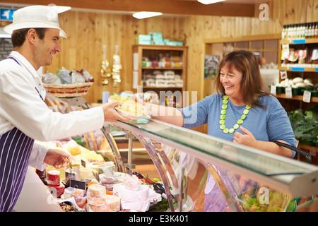 Maschio assistente di vendita di servire il cliente nel negozio di specialità gastronomiche Foto Stock