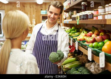 Assistant aiuta il cliente a contatore di vegetali di Farm Shop Foto Stock