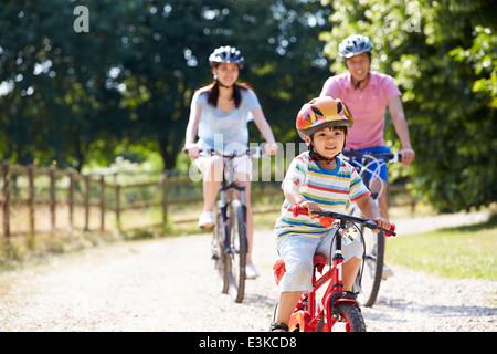 Famiglia asiatica sul tragitto in bicicletta in campagna Foto Stock