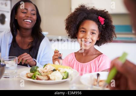 Madre e figlia avente famiglia pasto a tavola Foto Stock