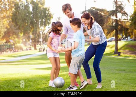 La famiglia che giocano a calcio nel parco insieme Foto Stock