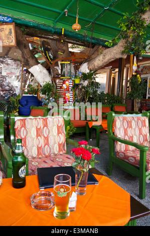 Un vetro stampato di Mythos Greco birra, Gin il posto della Turkish Cafe bar, Platani, Kos, Grecia, pub tavola bicchieri Foto Stock