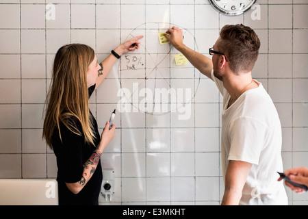 Young business persone mettere note adesive sul muro nel nuovo ufficio Foto Stock