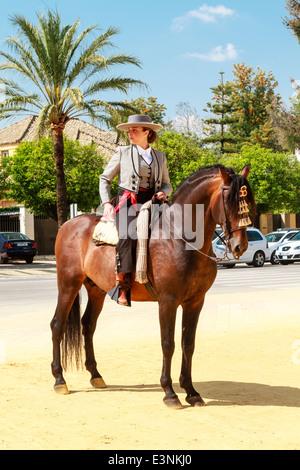 Pilota femmina decked out in flat-sormontato hat sul suo cavallo in piedi in strada durante la Feria del Caballon, Foto Stock