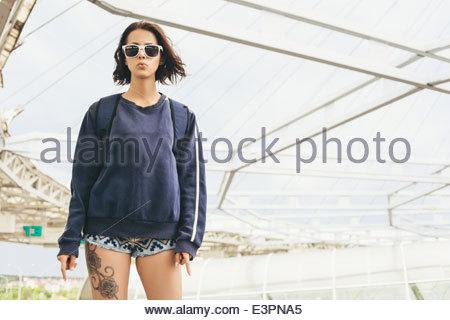Hipster ragazza adolescente in occhiali da sole con tattoo Foto Stock