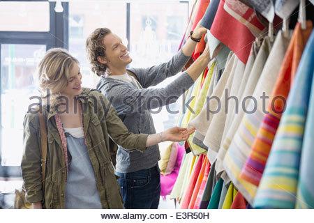 Giovane guardando al tessuto in negozio di biancheria Foto Stock