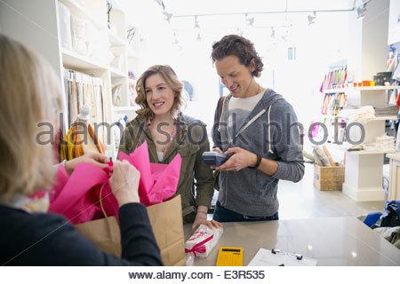 Giovane utilizzando il lettore di carte di credito in negozio Foto Stock