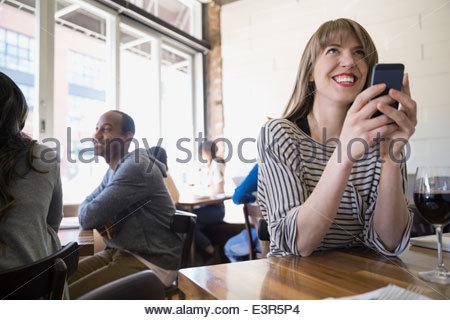 Donna sorridente con il cellulare in bistro Foto Stock