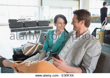Coppia sorridente in attesa in aeroporto Foto Stock