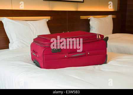 Red valigia sul letto in una stanza di un hotel Foto Stock