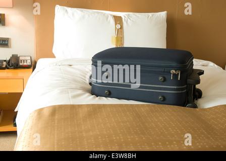 Valigia sul letto in una stanza di un hotel Foto Stock