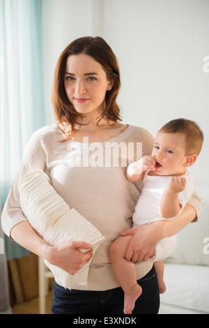 La madre del bambino di contenimento e la pila di pannolini