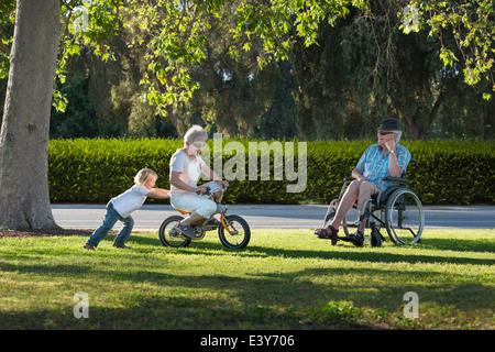 Tre anni di vecchio ragazzo spingendo la nonna sul ciclo con nonno guardando dalla sedia a rotelle Foto Stock