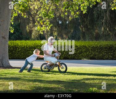 Tre anni di vecchio ragazzo spingendo la nonna sul ciclo in park Foto Stock