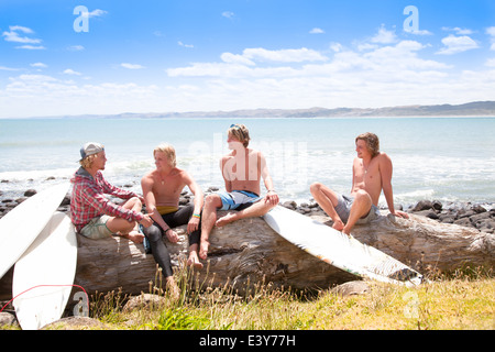 Quattro giovani maschi surfer amici in chat sulla spiaggia spiaggia di roccia Foto Stock