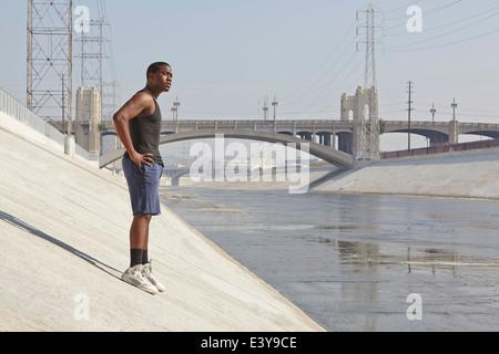 Giovane maschio runner prendendo una pausa in città riverbank Foto Stock