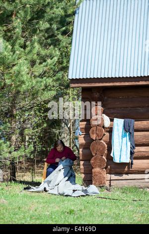 Senior needlewoman caucasica seduta in ombra e funzionante Foto Stock