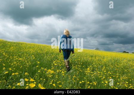 Donna che cammina nel campo di renoncules