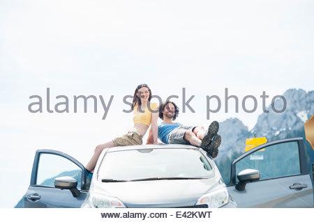 Metà adulto giovane rilassante sul tetto del veicolo, Wallberg, Tegernsee, Baviera, Germania Foto Stock