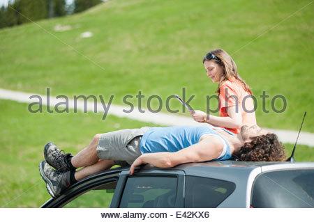 Metà adulto giovane rilassante sul tetto del veicolo Foto Stock