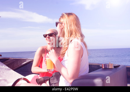 Due femmina adulta amici ridere a bordo di yacht Foto Stock