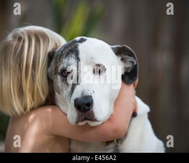 Ritratto di triste guardando cane abbracciato da tre anni di old boy Foto Stock