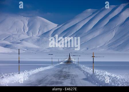 La strada che attraversa il Piano Grande in inverno. Parco Nazionale dei Monti Sibillini, Umbria, Italia, Febbraio Foto Stock