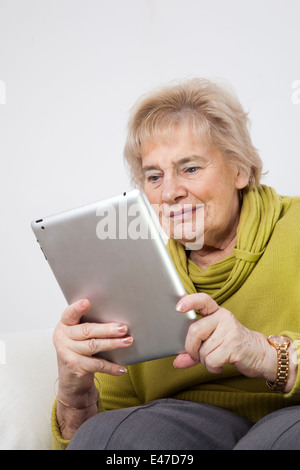 Senior lady guardando una tavoletta digitale (senza marca i-pad) Foto Stock
