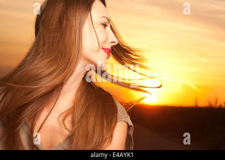 Bella e felice giovane donna in presenza di luce solare Foto Stock