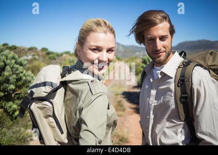 Escursionismo giovane camminando sul terreno di montagna sorridente in telecamera Foto Stock