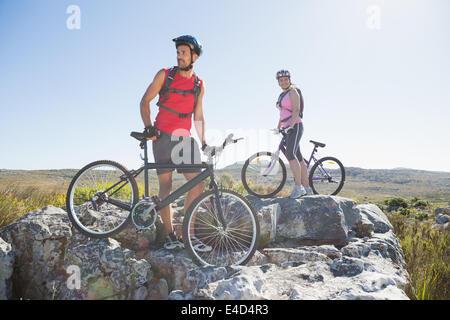 Montare il ciclista giovane in piedi al vertice guardando intorno Foto Stock