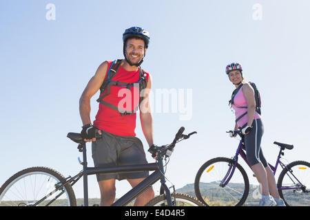 Montare il ciclista giovane in piedi al vertice sorridente in telecamera Foto Stock