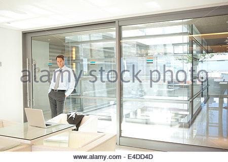 Imprenditore appoggiata contro la parete di vetro in office Foto Stock