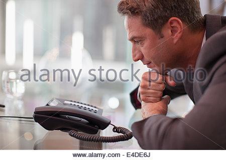Imprenditore staring al telefono in attesa di una chiamata Foto Stock