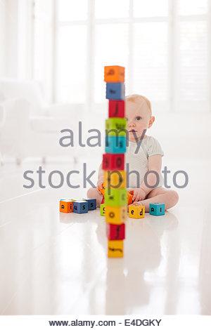 Bambino sul piano guardando impilati i blocchi di legno Foto Stock