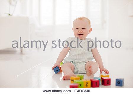 Baby mantenendo i blocchi di legno e craying Foto Stock