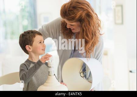 Figlio (6-7) e madre modifica lampadina nella lampada da tavolo
