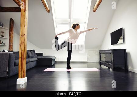 Femmina Fitness esercizio in salotto. Stretching e in equilibrio su una gamba sola a casa. Femmina caucasica la Foto Stock