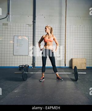 Montare la giovane donna in piedi in palestra con barbell sul pavimento. Forte e muscoloso crossfit femmina alla Foto Stock