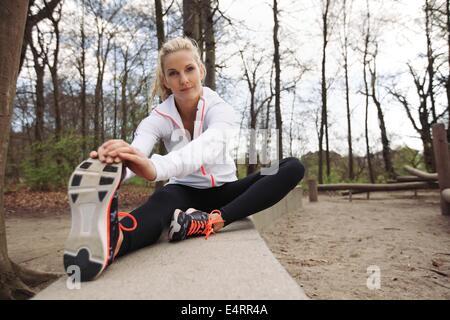 Bella giovane femmina fitness stretching prima di eseguire nel parco. La donna caucasica esercitando in natura. Foto Stock