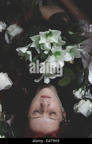 Innocenza, Teen sommerso in acqua con rose bianche, romance scena Foto Stock