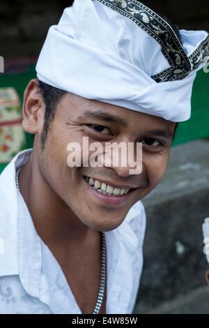 Bali, Indonesia. Giovane uomo indù indossando un Udeng, il tradizionale design Balinese testa maschio Wrap. Pura Foto Stock