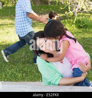 Una madre nel parco con sua figlia, ridendo e baciando ogni altro. Padre e figlio in esecuzione sull'erba. Foto Stock