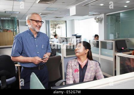 Senior l uomo e la donna avente una chat in ufficio Foto Stock