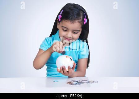 Ragazza sorridente mettendo le monete nel salvadanaio contro sfondo blu Foto Stock
